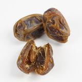 Dates sliced and whole on white background Stock Photo