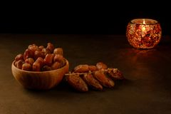Dates in wooden bowl and lantern on stone table. Muslim holy month Ramadan Kareem. Copy space royalty free stock photo