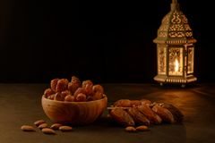Dates in wooden bowl and lantern on stone table. Muslim holy month Ramadan Kareem. Copy space stock photo