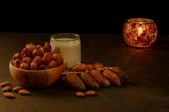 Dates in wooden bowl, milk and lantern on stone table. Muslim holy month Ramadan Kareem. Copy space stock image