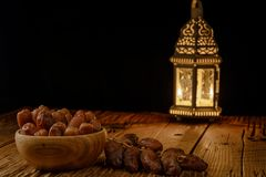 Dates in wooden bowl and lantern on wooden table. Muslim holy month Ramadan Kareem. Copy space royalty free stock images