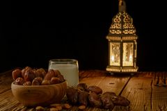 Dates in wooden bowl, milk and lantern on wooden table. Muslim holy month Ramadan Kareem. Copy space royalty free stock photos