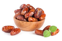 Dates in a wooden bowl with a mint leaf isolated on white background Royalty Free Stock Images