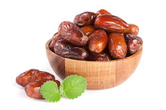 Dates in a wooden bowl with a mint leaf  on white background Stock Images