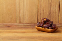 Dates on wooden plate with copy space Stock Images