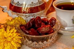 Dates on wooden table with flowers and retro dishes stock images
