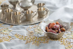 Dates and zam zam water cups on white table cloth Royalty Free Stock Images