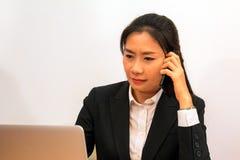 Dati asiatici di chiamata e del controllo della donna dal computer portatile Fotografia Stock