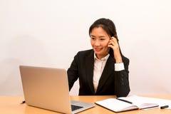 Dati asiatici di chiamata e del controllo della donna dal computer portatile Fotografie Stock