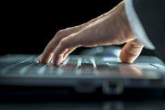 Dati entranti dell'uomo sul suo computer portatile Fotografie Stock Libere da Diritti
