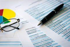 Dati finanziari di stima del foglio elettronico delle azione di attività bancarie Penna, occhiali e grafici immagini stock