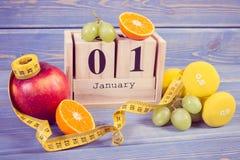 Dati il 1° gennaio sul calendario, sui frutti, sulle teste di legno e sulla misura di nastro, nuovi anni di concetto di risoluzio Immagine Stock
