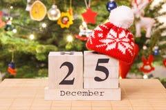 Dati il 25 dicembre con il cappuccio e l'albero festivo con la decorazione nel fondo, concetto di tempo di Natale Fotografia Stock