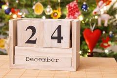 Dati il 24 dicembre sul calendario, albero festivo con la decorazione nel fondo, concetto di tempo di notte di Natale Immagini Stock