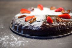 Datieren Sie den Kuchen, der mit Zucker, trockenen Daten und frischen Erdbeeren verziert wird Stockbild