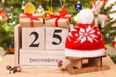 Datieren Sie am 25. Dezember auf Kalender, Geschenke mit Schlitten und Kappe, Weihnachtsbaum mit Dekoration, festliches Zeitkonze Stockfotos