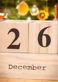 Datieren Sie am 26. Dezember auf Würfelkalender, festlicher Baum mit Dekoration im Hintergrund, Weihnachtszeit Stockfotografie