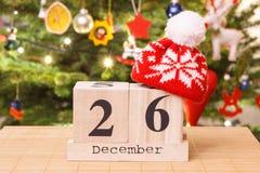 Datieren Sie am 26. Dezember mit Kappe und festlichem Baum mit Dekoration im Hintergrund, Weihnachtszeitkonzept Stockfoto
