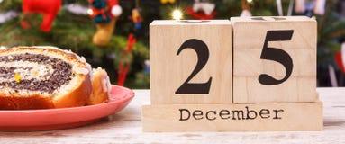 Datieren Sie am 25. Dezember, Mohn Kuchen und Weihnachtsbaum mit Dekoration im Hintergrund Stockfotografie