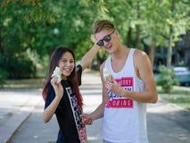 Datierungsmädchen und -junge, die Eiscreme auf einem Parkhintergrund essen Romantische, nette entspannende Paare Abgehendes Leben Lizenzfreies Stockbild