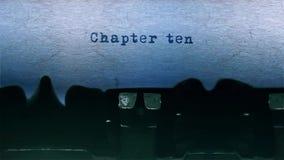 A datilografia da palavra do capítulo dez centrou-se em uma folha de papel no áudio velho da máquina de escrever vídeos de arquivo