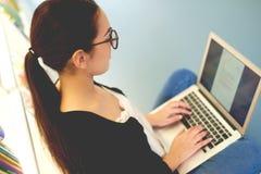 Datilografia de assento da jovem mulher em seu portátil Fotos de Stock Royalty Free