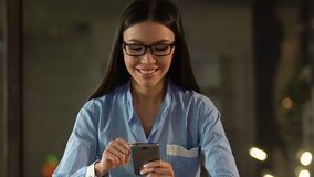 Datilografia fêmea de sorriso no smartphone que surfa na rede social, cargos de comentário vídeos de arquivo