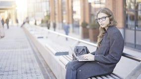 Datilografia nova da mulher de negócios exterior e vista de você Foto de Stock Royalty Free