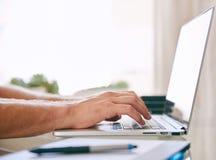 Datilografia ocupada das mãos brancas em um laptop Fotografia de Stock