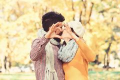 Dating and autumn love concept. Couple in love with scarves. Shows heart sign with fingers. Girl and bearded guy or happy lovers on a date kiss. Man and women royalty free stock photos