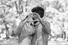 Dating and autumn love concept. Couple in love with scarves. Shows heart sign with fingers. Girl and bearded guy or happy lovers on a date kiss. Man and women stock image