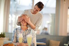 Dating in cafe. Young men covering his girlfriend eyes to make her surprise while sitting in cafe royalty free stock images