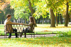 Dating couple on a bench. By fall royalty free stock photo