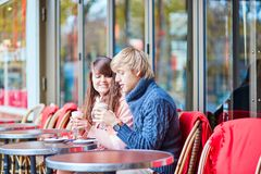 Dating couple drinking coffee in a Parisian cafe Stock Photos