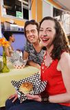 Dating couple having burgers smile at camera stock photography