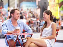 Dating couple, New York, Manhattan, Times Square. Dating drinking coffee smiling happy sitting at red tables enjoying their tourism vacation travel in the USA stock image