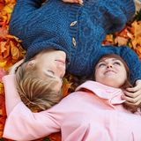 Dating couple in Paris on a fall day. Young dating couple in Paris on a bright fall day lying on the ground in autumn leaves Stock Images