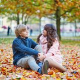 Dating couple in Paris on a fall day. Young dating couple in Paris on a bright fall day sitting on the ground in autumn leaves stock photo