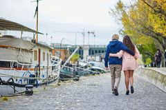Dating couple in Paris on a fall day. Young dating couple in Paris on a bright fall day, walking together by the Seine, colorful autumn leaves in the background royalty free stock photo
