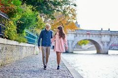 Dating couple in Paris on a fall day. Young dating couple in Paris on a bright fall day, walking together by the Seine, colorful autumn leaves in the background royalty free stock photography