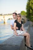 Dating couple in Paris. Sitting on the Seine embankment stock image