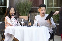 Dating Couple Paying at a Restaurant. Female hustler on a date with a gullible men paying for her restaurant bill in an outdoor cafe.  The image depicts Royalty Free Stock Photography