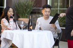 Dating Couple Paying at a Restaurant. Female hustler on a date with a gullible men paying for her restaurant bill in an outdoor cafe.  The image depicts Royalty Free Stock Photos
