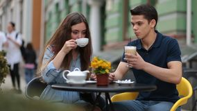 Dating couple relaxing together in street cafe stock footage