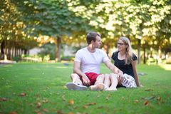 Dating couple sitting on the grass in park Stock Image