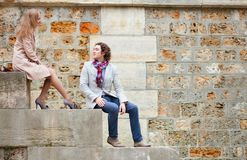 Dating couple sitting on the Seine embankment Stock Photos