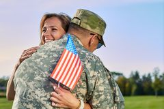 Dating of happy woman and her husband us army soldier. Dating of happy women and her husband us army soldier. Wife with us flag is hugging her military husband royalty free stock photos