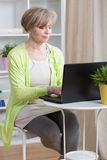 Dating online on laptop. Attractive mature woman dating online on laptop royalty free stock photography