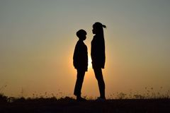 Dating on the sunset. Silhouette of the couple standing on sunset. Concept dating in the sunset Royalty Free Stock Images