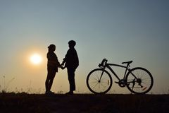 Dating on the sunset. Silhouette of the couple standing hand in hand with bicycle on sunset. Concept dating on the sunset royalty free stock photography